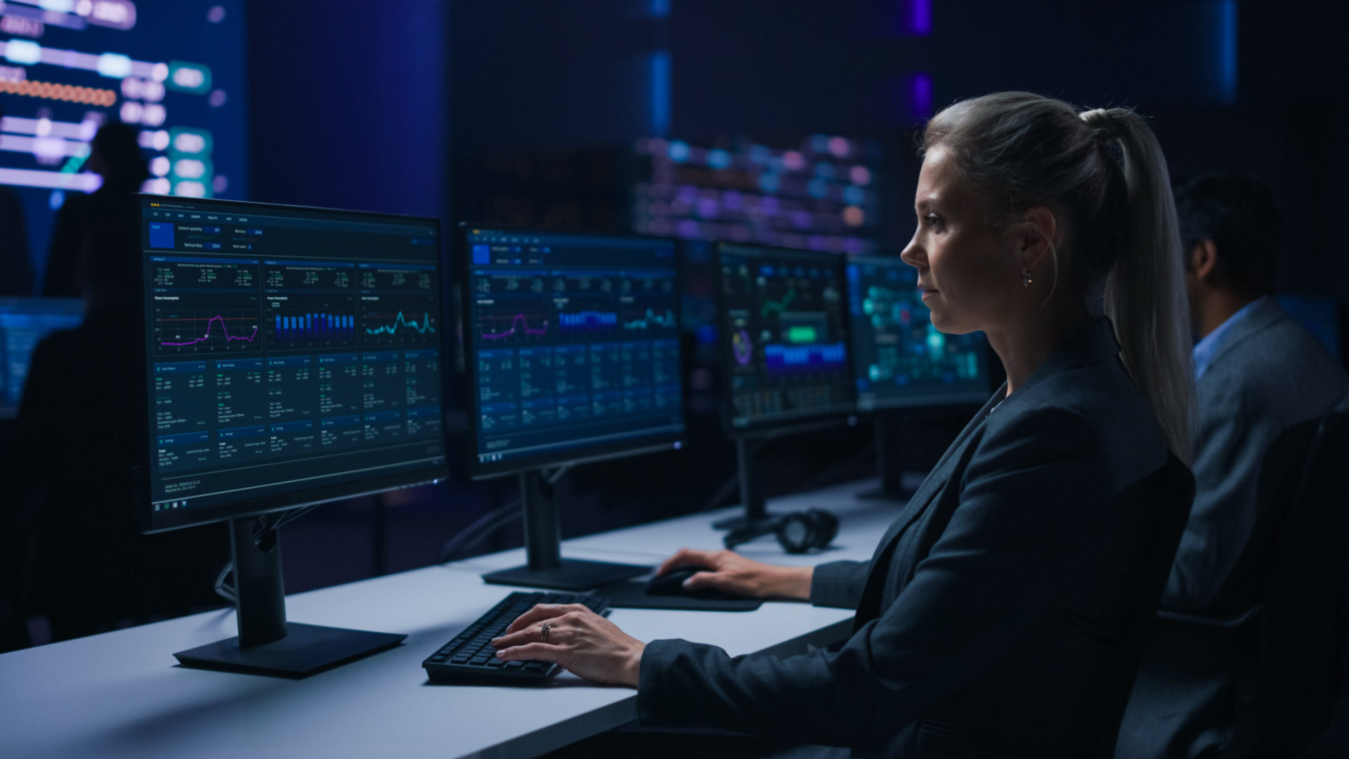 Confident Female Data Scientist Works on Personal Computer in Big Infrastructure Control Room. Team of Stock Market Specialist Use Computers Showing Global Map, Graphs, Charts, Information